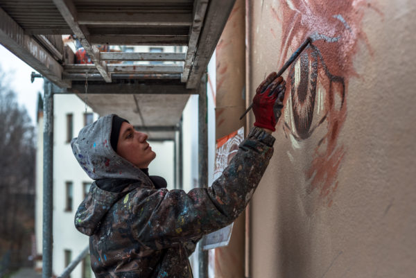 Mężczyzna stoi na rusztowaniu i pędzlem maluje mural.