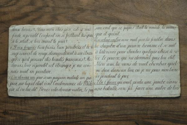 Otwarty podniszczony zeszyt z pięknie zapisanymi literami.