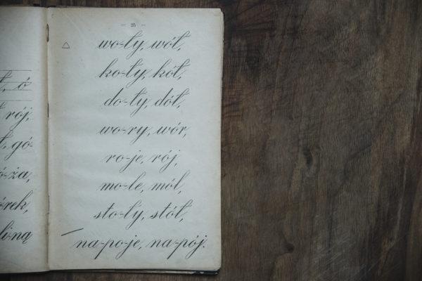 Na drewnianym blacie leży otwarty zeszyt, w którym znajdują się pięknie zapisane wyrazy.