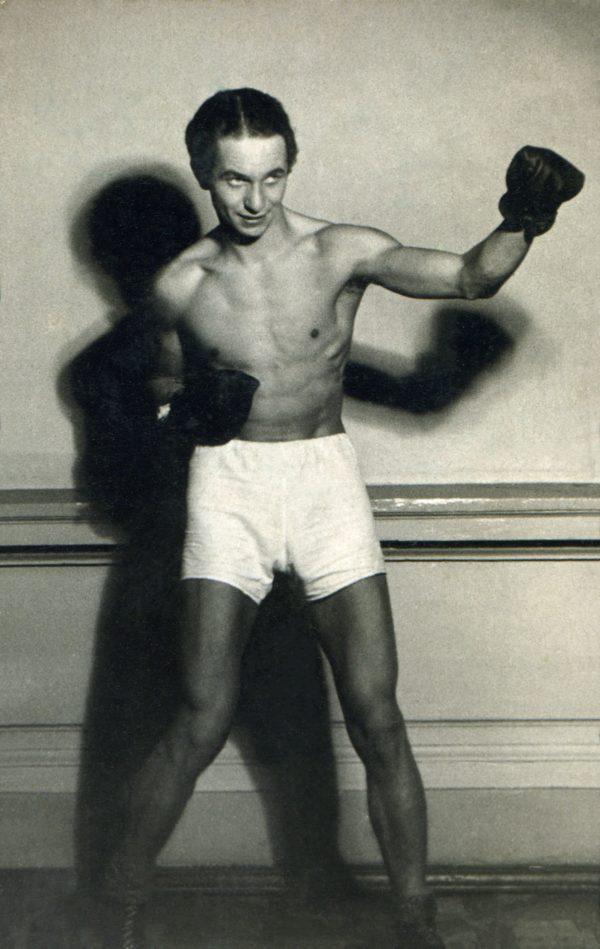 Mężczyzna ubrany w strój bokserski, pozuje do zdjęcia.