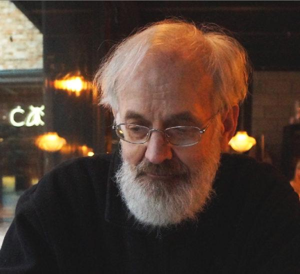 Starszy mężczyzna o siwych włosach i zaroście, siedzi w lokalu.