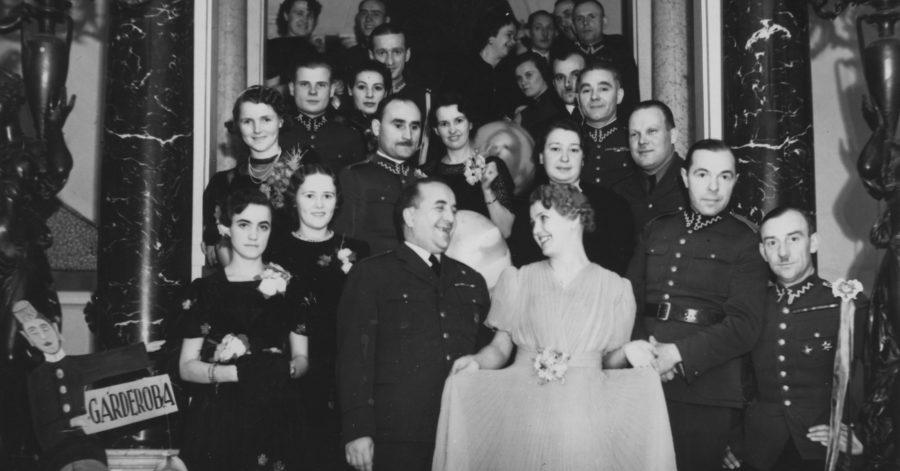 Czarnobiałą fotografia przedstawia, grupę elegancko ubranych ludzi, którzy pozują do zdjęcia w eleganckiej sali.