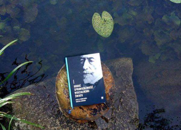 Na pieńku częściowo zanurzonym w jeziorze leży książka. Na jej okładce znajduje się portret mężczyzny z brodą.