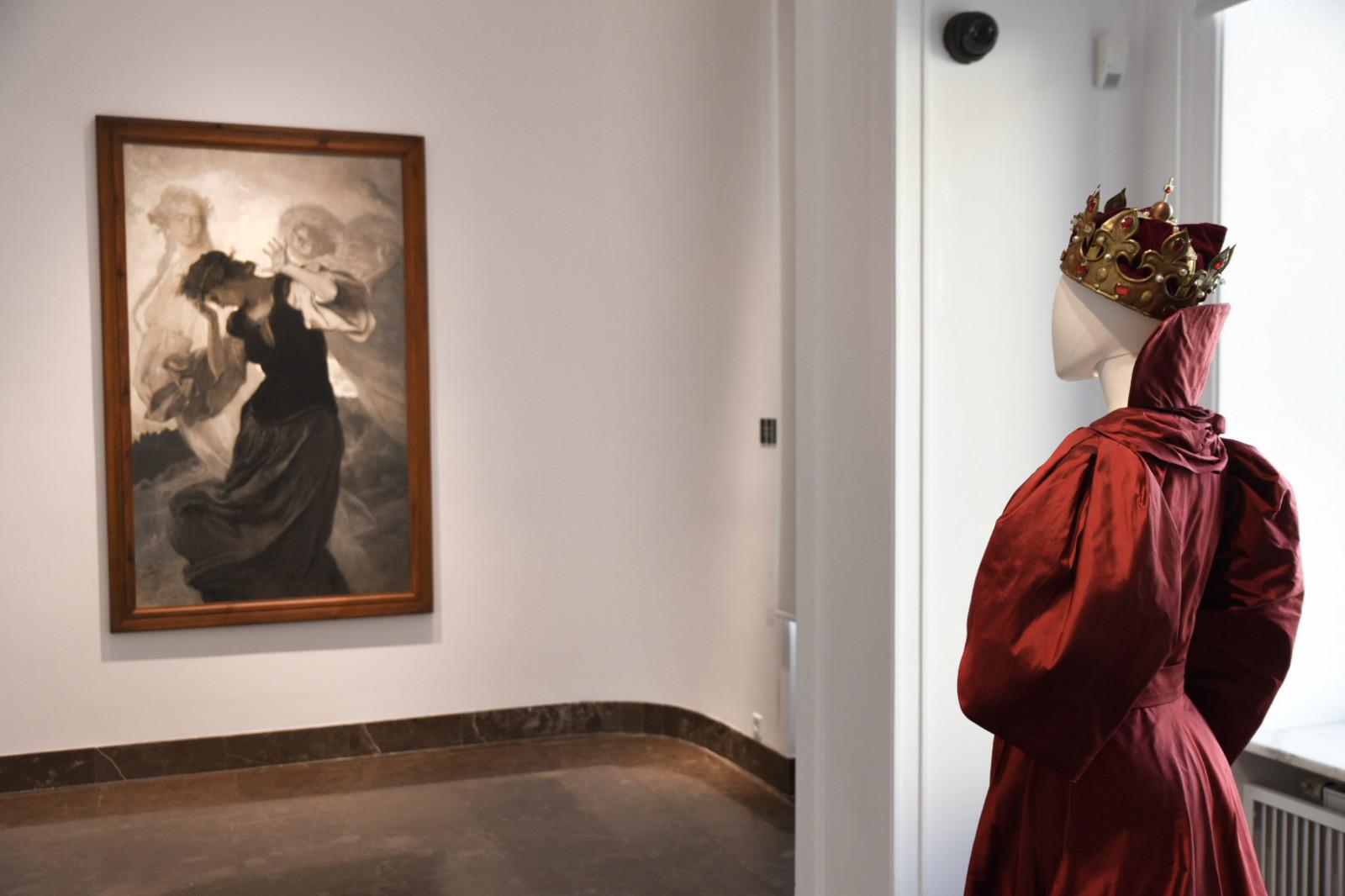 Manekin, ubrany w strój królowej, stoi na przeciwko obrazu rozchwianej kobiety.