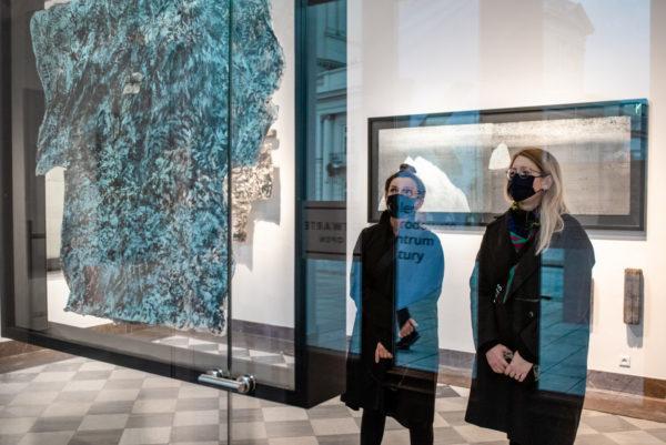 Dwie kobiety w maseczkach przyglądają się abstrakcyjnej płaskorzeźbie umieszczonej w szkle.
