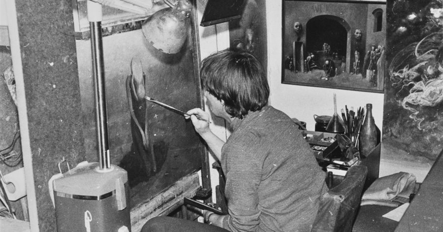 Mężczyzna maluje kobietę na płótnie.