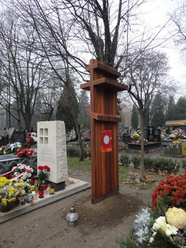 Drewniany, wysoki krzyż prawosławny stoi wbity w ziemię. Przed nim znajduje się jeden znicz.