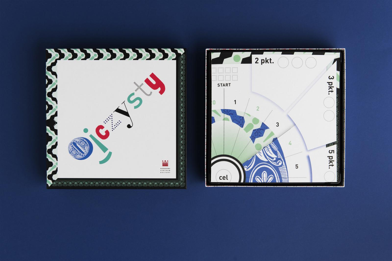"""Górna część pudełka gry leży obok zwiniętej planszy do gry. Okładka gry przedstawia napis: """"ojczysty"""", każda litera jest napisana innym fontem i ma różny kolor."""