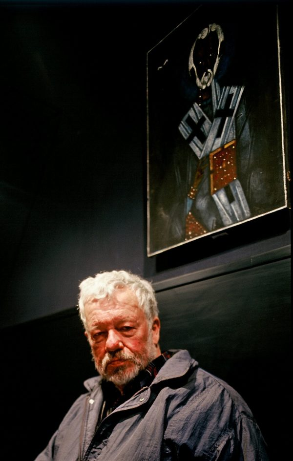 Starszy mężczyzna siedzi na ławce, nad nim wisi portret innego mężczyzny.