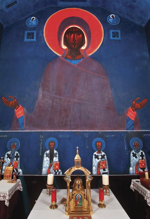Wielki portret Matki Boskiej namalowany na kamiennej ścianie. Poniżej znajdują się cztery mniejsze portretu świętych.