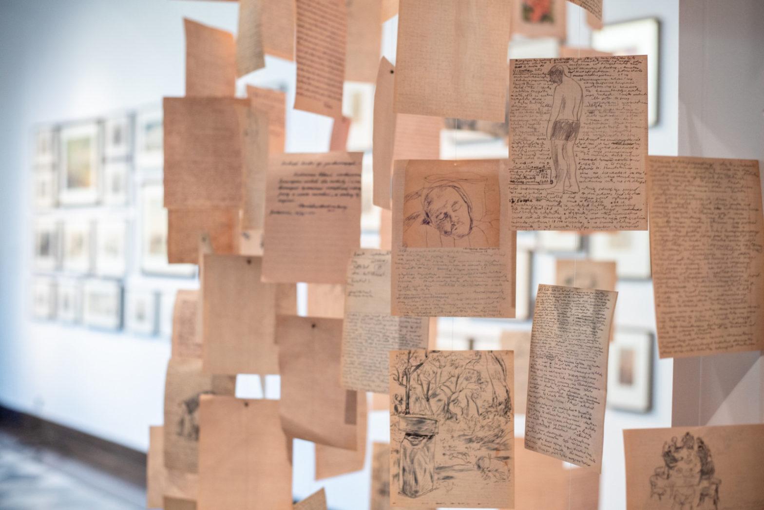 Fragment ekspozycji przedstawia zawieszone na żyłkach kartki z rysunkami i tekstami.