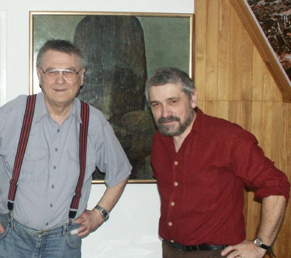 Dwójka mężczyzn w średnim wieku pozuje na tle obrazu.