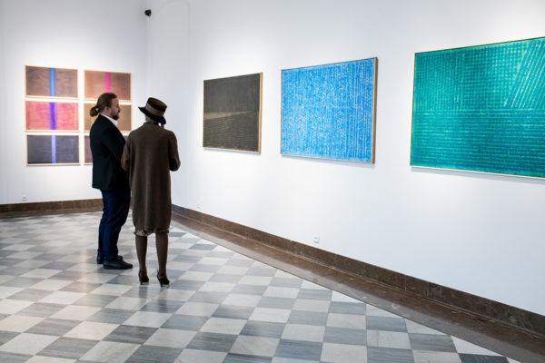 Kobieta i mężczyzna oglądają obrazy wiszące na ścianie.