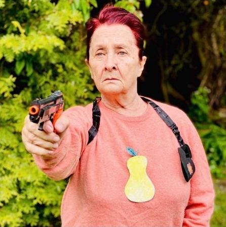 Kobieta w swetrze z gruszką na jego środku, celuje z zabawkowego pistoletu.