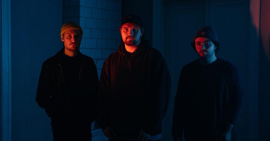 Trzech mężczyzn pozuje w ciemnym pomieszczeniu.