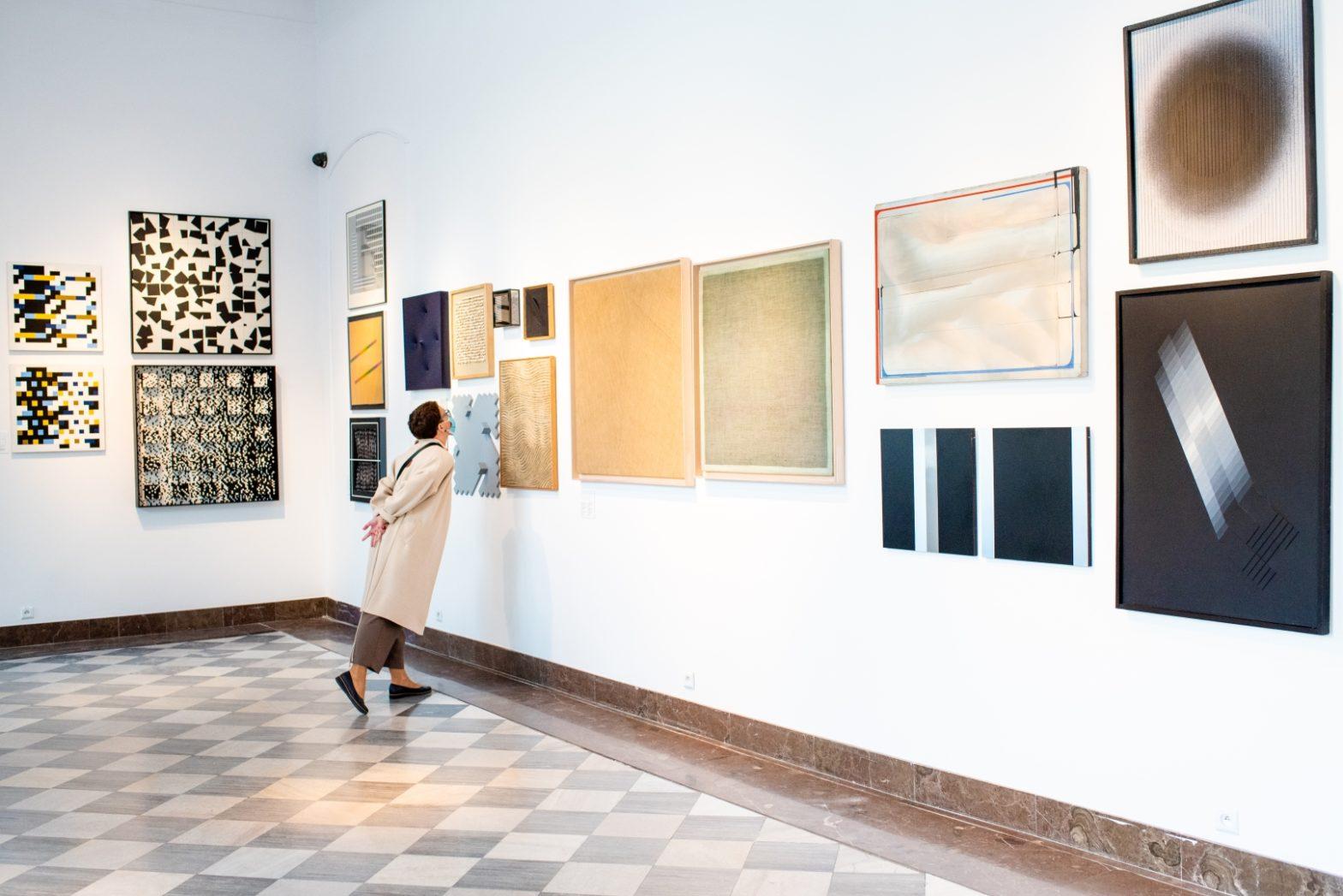 Kobieta przygląda się obrazowi w muzeum.