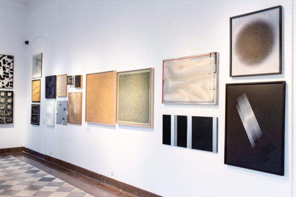 Fragment ekspozycji: obrazy abstrakcyjne wiszące na ścianach.