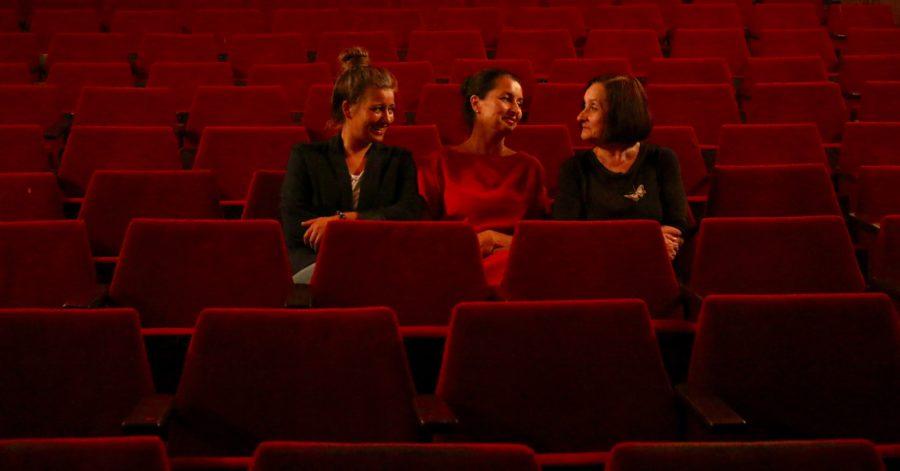 Trzy kobiety rozmawiają w pustej sali kinowej.