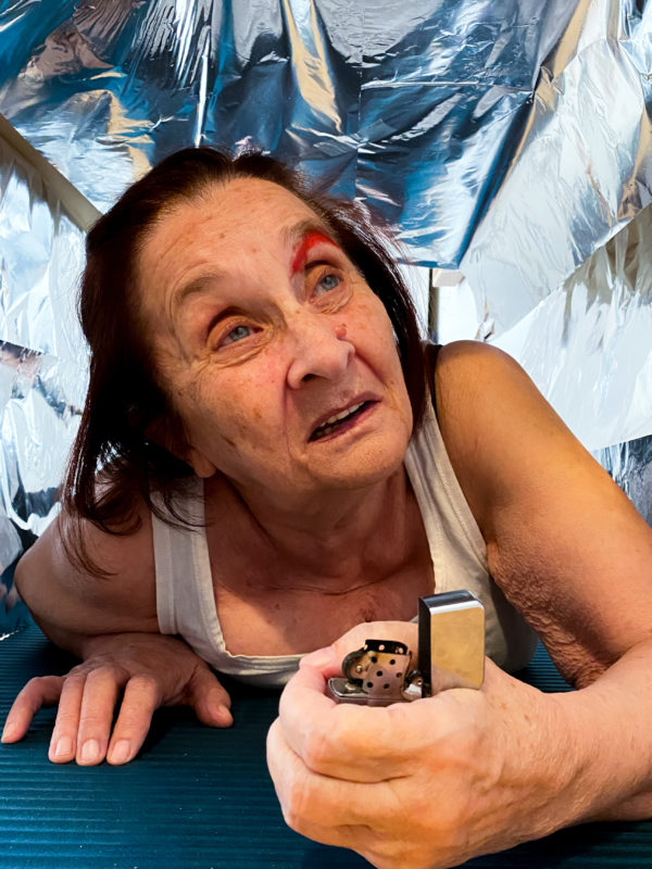 Kobieta czołga się w szybie wentylacyjnym, w ręce trzyma zapalniczkę.