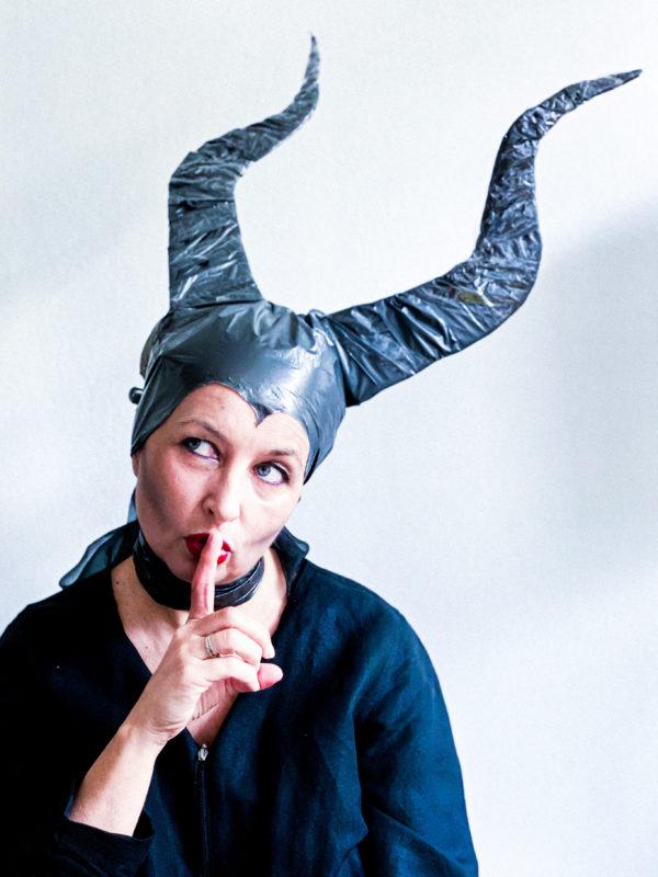 Kobieta wykonuje gest uciszenia. Na głowie ma założone wielkie ciemne rogi.