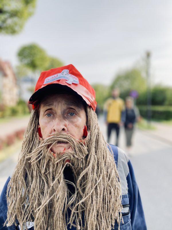 Osoba przebrana za zapuszczonego człowieka w starych ubraniach i z długimi zniszczonymi włosami.