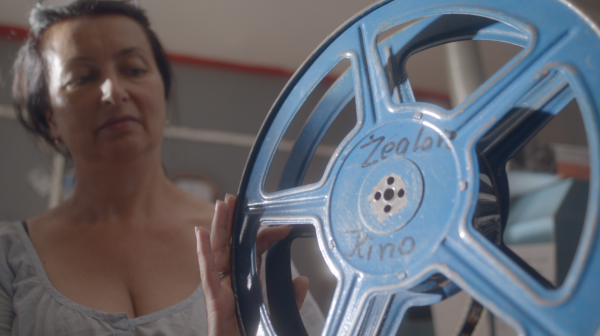 """Kobieta z pustą szpulą filmową z napisem """"Kino Żeglarz""""."""
