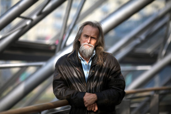 Mężczyzna z długimi włosami i brodą, stoi oparty o barierkę.