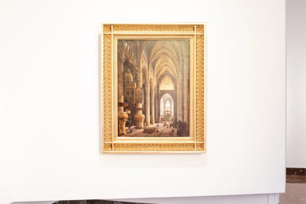 """Fragment ekspozycji, oprawiony w ramkę obraz """"Wnętrze Katedry w Mediolanie"""" wisi na białej ścianie."""