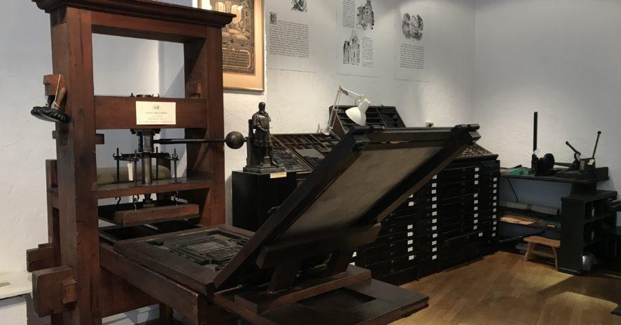 Fragment ekspozycji: drewniano-metalowe urządzenia drukarskie stoją na podłodze, na ścianach wiszą opisane ryciny.