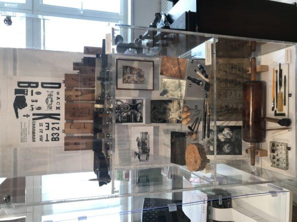 Przeszklona gablota, w której znajdują się drobne narzędzia oraz fotografie - fragment ekspozycji.