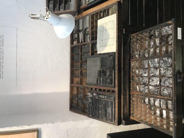 Fragment ekspozycji: drewniany mebel z szufladami podzielonymi na przegródki, w których znajdują się drobne, metalowe elementy.