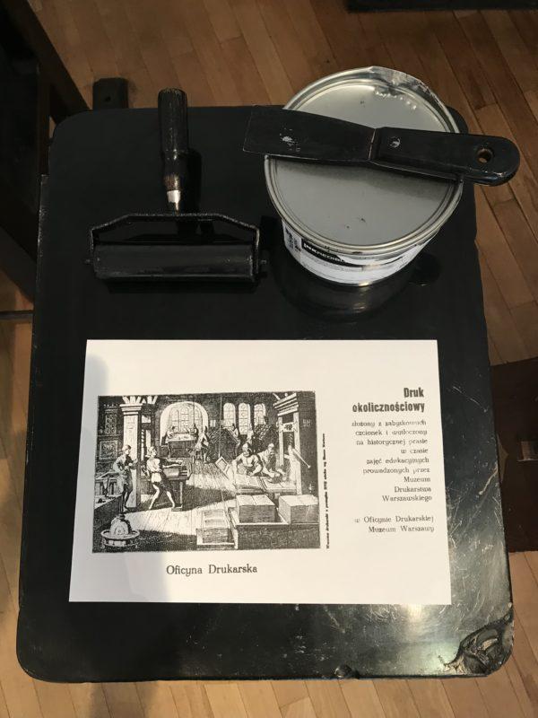 """Fragment ekspozycji: na drewnianym stoliku leży wiadro z farbą, narzędzia drukarskie oraz rycina podpisana """"oficyna drukarska""""."""