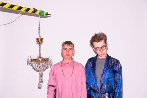 Dwóch młodych mężczyzn kolorowo ubranych pozuje z bogato zdobioną lampą, zawieszoną obok nich.