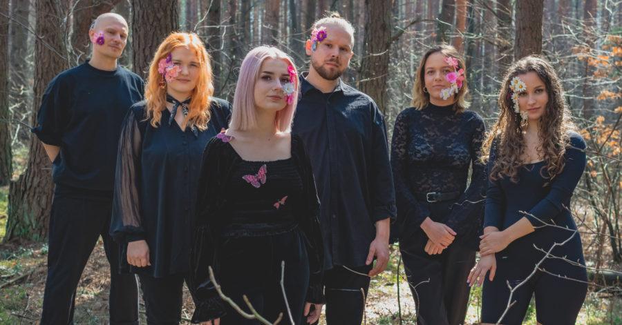 Sześcioosobowy zespół pozuje w lesie.