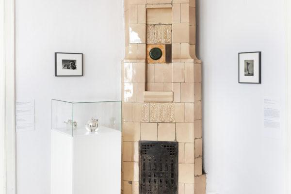 Piec kaflowy dzieli pomieszczenie na dwie części, po jednej stronie wisi pojedynczy obraz oprawione w ramce; po drugiej symetrycznie do pierwszego - wisi drugi obraz, a pod nim znajduje się gablota.