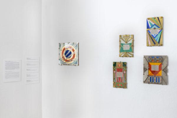 Fragment ekspozycji, jaskrawe obrazy są zawieszone na białej ścianie.