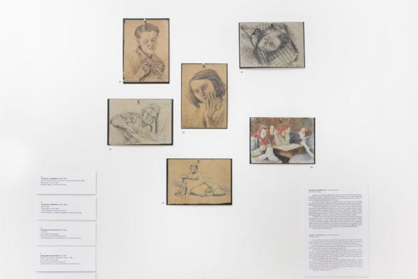 Fragment ekspozycji, rysunki zawieszone na białej ścianie, opatrzone