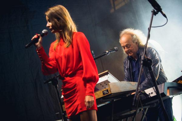 Młoda wokalistka śpiewa na scenie, za nią siedzi starszy mężczyzna, który gra na klawiszach.