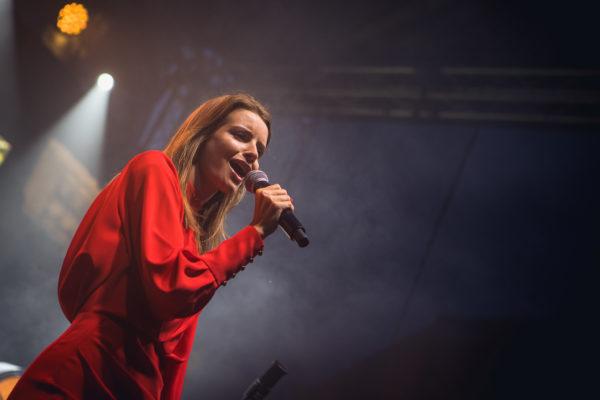 Młoda wokalistka śpiewa na scenie.