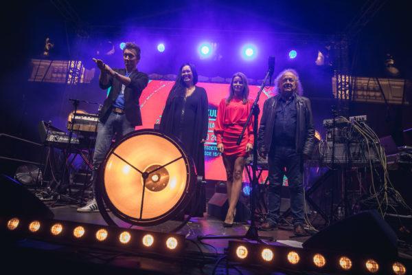 Czteroosobowy zespół na scenie, żegna się z publicznością.