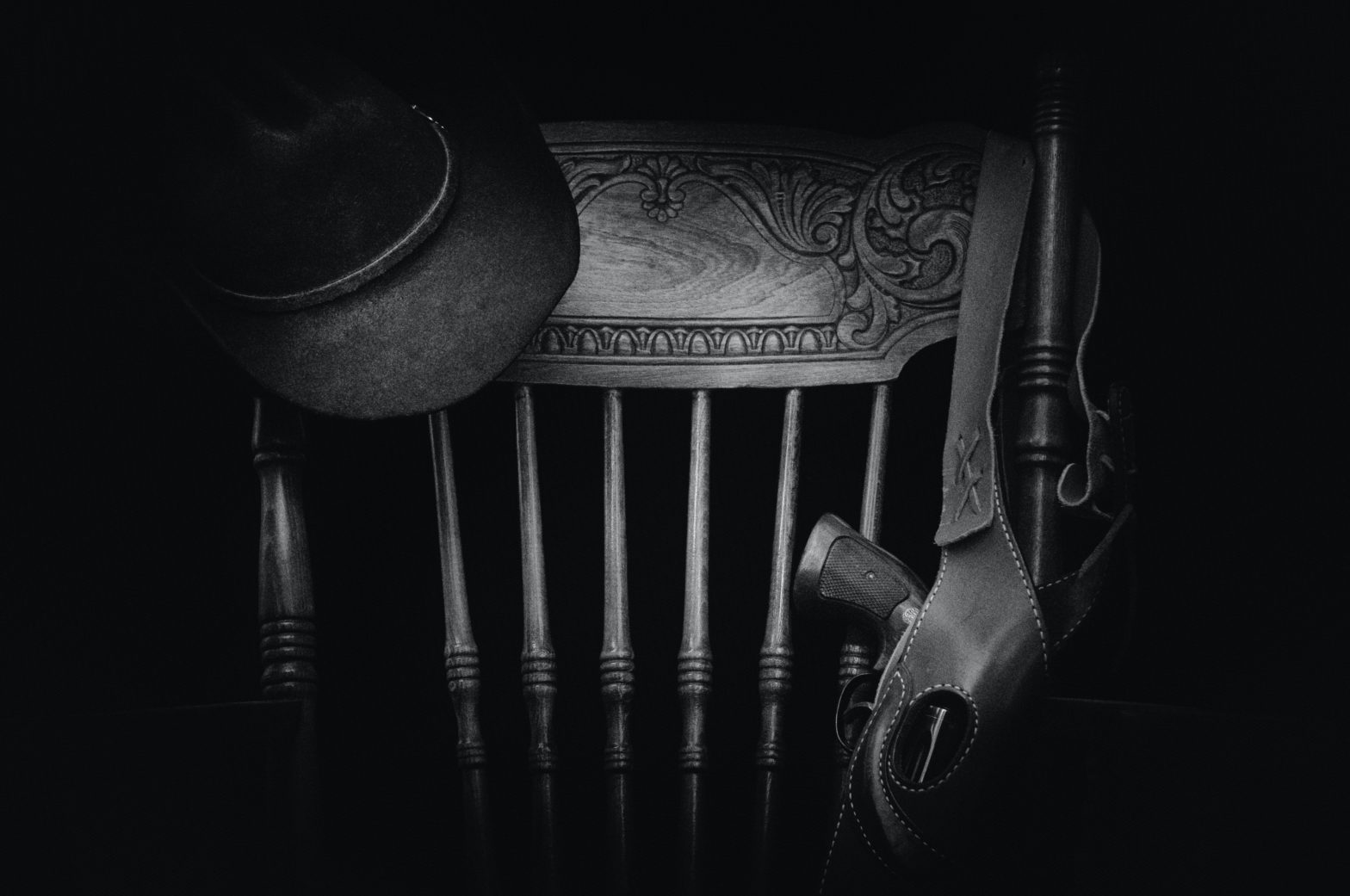Krzesło, na którym zawieszony jest kapelusz i kabura z rewolwerem.