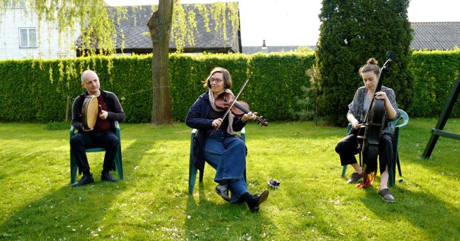Trzyosobowy zespół odgrywa koncert na trawniku.